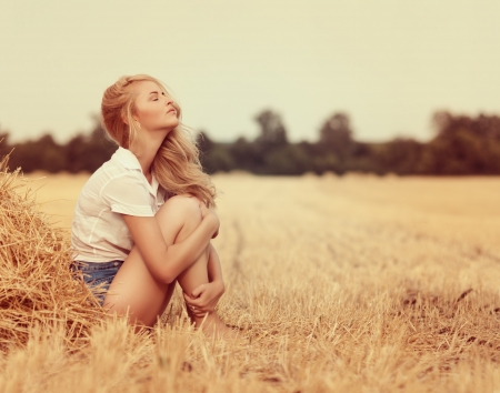 Photo for Attractive young woman near the stacks of straw - Royalty Free Image