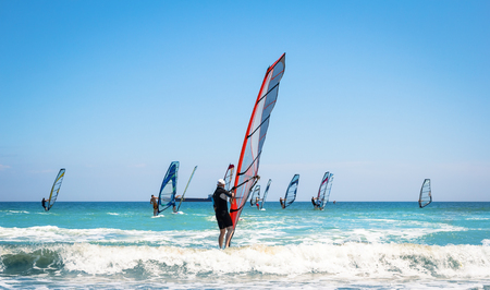 Photo pour Windsurfing sails on the blue sea riding the wind - image libre de droit