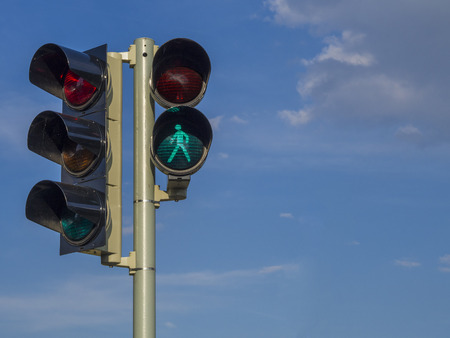 Foto de traffic light - semaphore - green walking figure puppet on blue sky background - Imagen libre de derechos