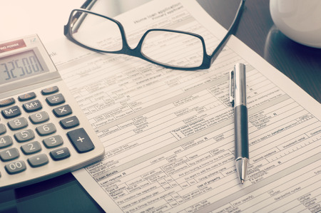 Photo pour Close up of a bank home loan  application form on desk with calculator and eye glasses - image libre de droit