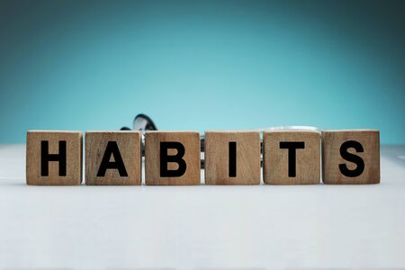 Foto per What is your habits? Sign with the word habits on white desk in a blue backgroud - Immagine Royalty Free
