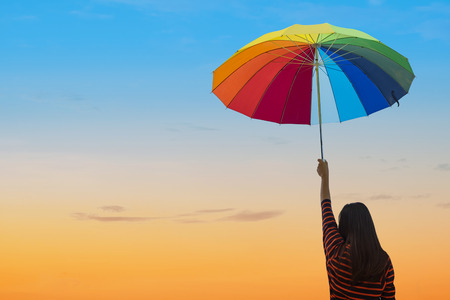 Happy Woman holding umbrella on Sunset