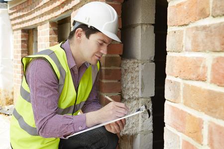 Photo pour Architect Checking Insulation During House Construction - image libre de droit