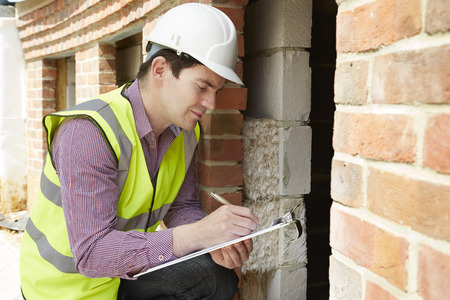 Foto de Architect Checking Insulation During House Construction - Imagen libre de derechos