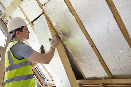 Photo pour Builder Fitting Insulation Into Roof Of New Home - image libre de droit