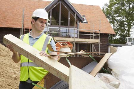 Photo pour Builder Putting Waste Into Rubbish Skip - image libre de droit