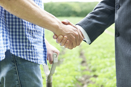 Photo for Farmer And Businessman Shaking Hands - Royalty Free Image