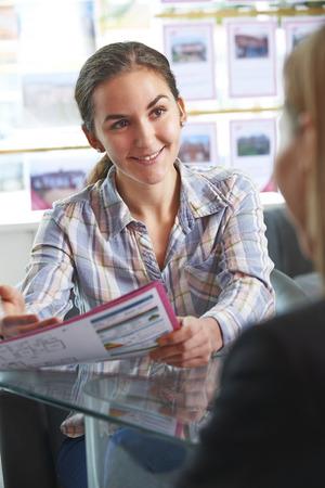 Photo pour Estate Agent Discussing Property With Client In Office - image libre de droit