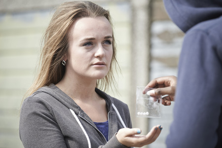 Photo pour Teenage Girl Buying Drugs On The Street From Dealer - image libre de droit