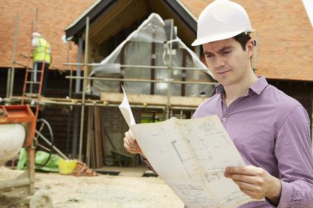 Foto de Architect On Building Site Looking At House Plans - Imagen libre de derechos