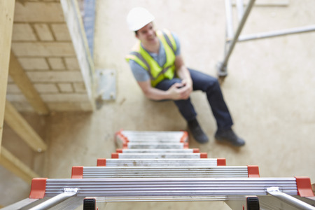 Photo for Construction Worker Falling Off Ladder And Injuring Leg - Royalty Free Image