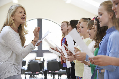 Photo for Children In Singing Group Being Encouraged By Teacher - Royalty Free Image
