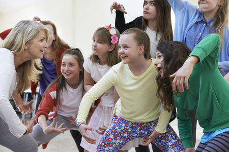 Foto de Group Of Children With Teacher Enjoying Drama Class Together - Imagen libre de derechos