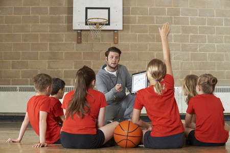 Foto de Coach Giving Team Talk To Elementary School Basketball Team - Imagen libre de derechos