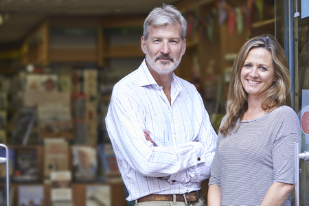Photo pour Portrait Of Couple Who Own Bookshop Outside Store - image libre de droit