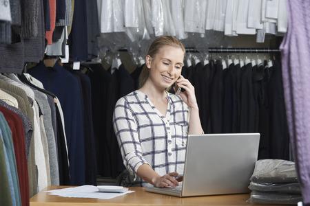 Photo pour Businesswoman Running On Line Fashion Business On The Phone - image libre de droit