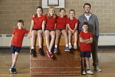 Foto de Portrait Of School Gym Team Sitting On Vaulting Horse - Imagen libre de derechos