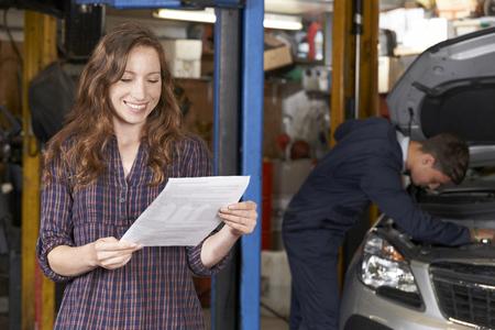 Photo pour Female Customer In Auto Repair Shop Satisfied With Bill For Car Repair - image libre de droit