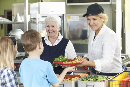 Photo pour Pupils In School Cafeteria Being Served Lunch By Dinner Ladies - image libre de droit