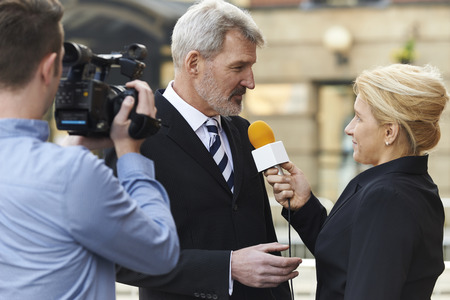 Photo for Female Journalist With Microphone Interviewing Businessman - Royalty Free Image