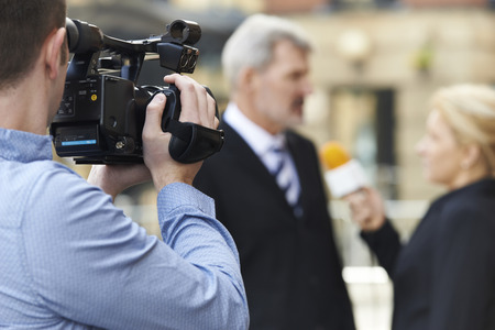 Photo for Cameraman Recording Female Journalist Interviewing Businessman - Royalty Free Image