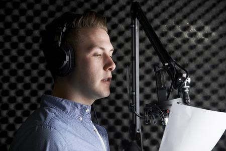 Photo pour Man In Recording Studio Talking Into Microphone - image libre de droit