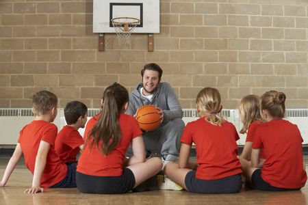 Photo pour Coach Giving Team Talk To Elementary School Basketball Team - image libre de droit