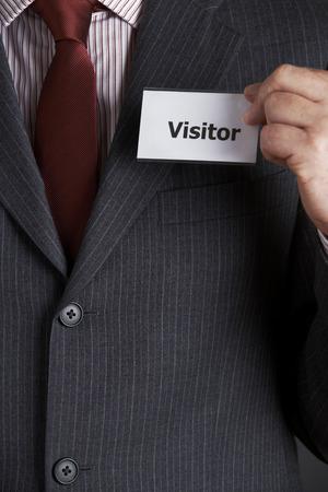 Foto de Businessman Attaching Visitor Badge To Jacket - Imagen libre de derechos
