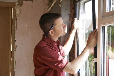 Photo pour Construction Worker Installing New Windows In House - image libre de droit