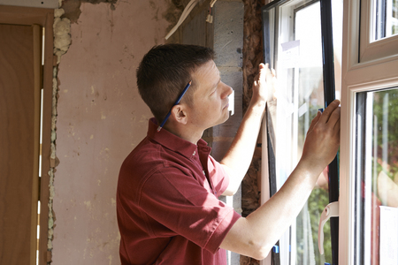 Foto de Construction Worker Installing New Windows In House - Imagen libre de derechos