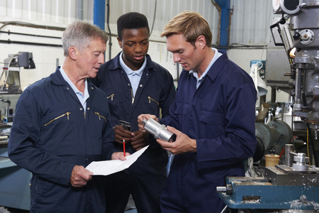 Photo pour Team Of Engineers Having Discussion In Factory - image libre de droit