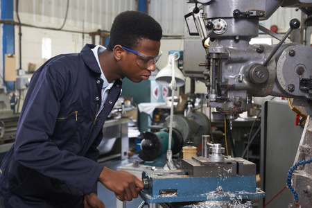 Photo pour Male Apprentice Engineer Working On Drill In Factory - image libre de droit
