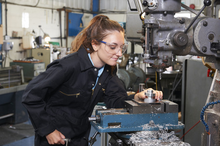 Photo pour Female Apprentice Engineer Working On Drill In Factory - image libre de droit