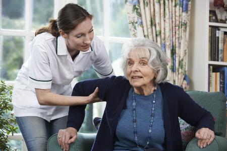 Foto de Care Worker Helping Senior Woman To Get Up Out Of Chair - Imagen libre de derechos