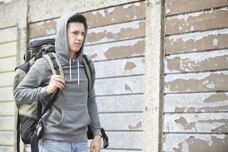 Foto de Homeless Teenage Boy On Street With Rucksack - Imagen libre de derechos