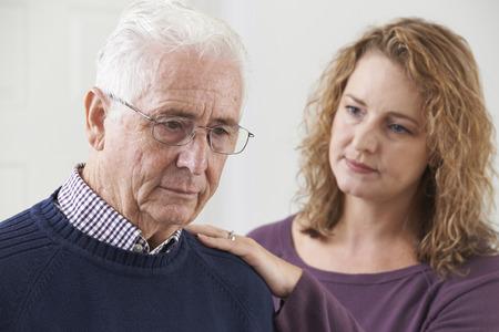 Foto de Serious Senior Man With Adult Daughter At Home - Imagen libre de derechos