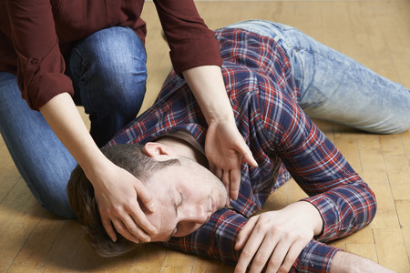Photo for Woman Placing Man In Recovery Position After Accident - Royalty Free Image