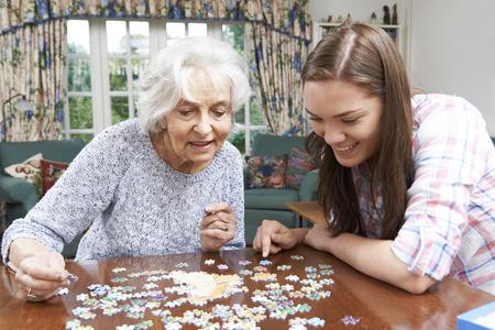 Foto de Teenage Granddaughter Helping Grandmother With Jigsaw Puzzle - Imagen libre de derechos