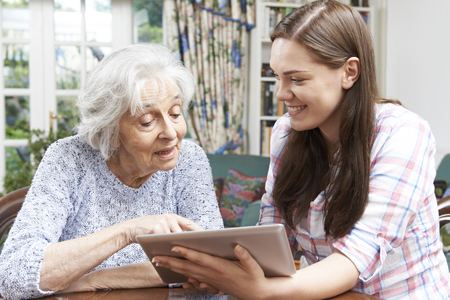 Photo for Teenage Granddaughter Showing Grandmother How To Use Digital Tablet - Royalty Free Image