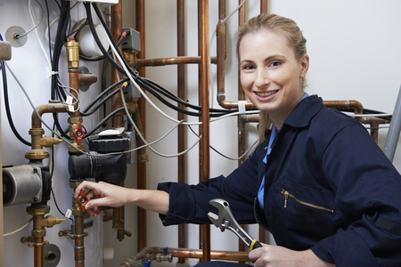 Photo for Female Plumber Working On Central Heating Boiler - Royalty Free Image
