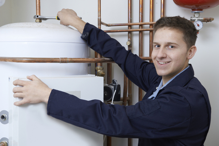Photo for Portrait Of Male Plumber Working On Central Heating Boiler - Royalty Free Image