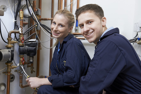 Photo for Female Trainee Plumber Working On Central Heating Boiler - Royalty Free Image