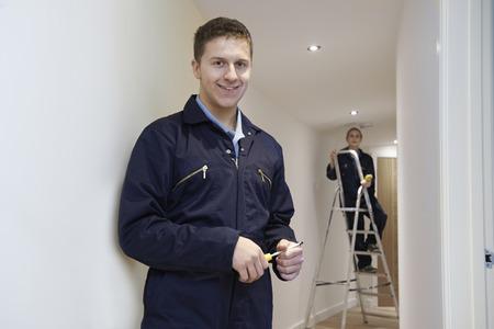 Foto de Electricians Installing Ceiling Lights In Domestic Home - Imagen libre de derechos