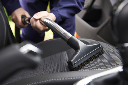 Photo pour Man Hoovering Seat Of Car During Car Cleaning - image libre de droit