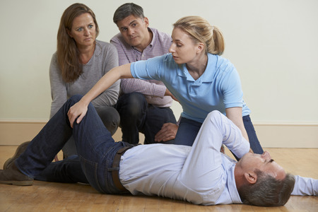 Photo for Woman Demonstrating Recovery Position In First Aid Training Class - Royalty Free Image