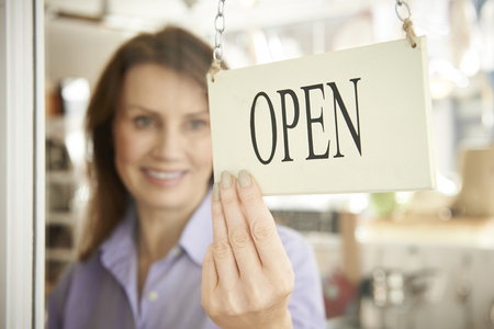 Photo pour Store Owner Turning Open Sign In Shop Doorway - image libre de droit