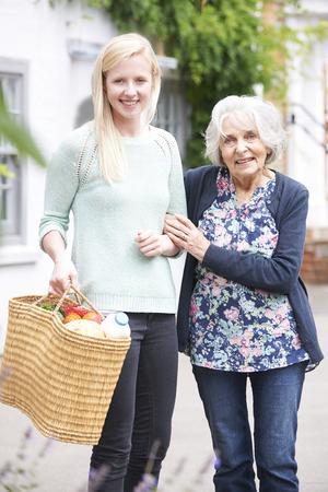 Foto de Teenage Girl Helping Senior Woman To Carry Shopping - Imagen libre de derechos