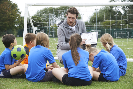 Foto de Coach Giving Team Talk To Elementary School Soccer Team - Imagen libre de derechos
