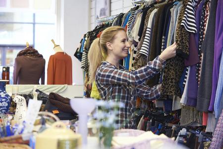 Foto de Female Shopper In Thrift Store Looking At Clothes - Imagen libre de derechos