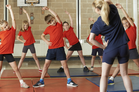 Photo for Teacher Taking Exercise Class In School Gym - Royalty Free Image